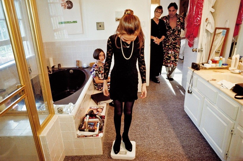 Ashleigh 13 weighs herself in her parents bathroom with her friend and parents in Santa Monica, California. (© Lauren Greenfield/Institute)